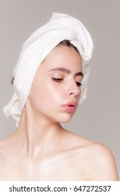 Cute girl or pretty woman with pure face skin, no make up, and white bath towel on head posing on grey background. Haircare, spa, natural beauty, hygiene