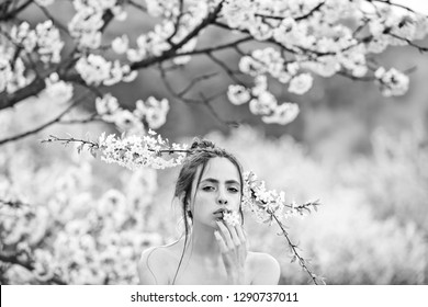 cute girl or pretty woman with white, blossoming flowers in mouth and hair posing with naked shoulders in spring garden on sunny day on blurred floral environment. Youth and natural beauty