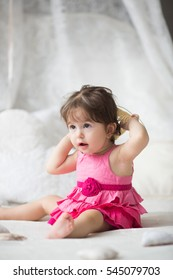 Cute girl, princess, a child in a pink dress on the white bed