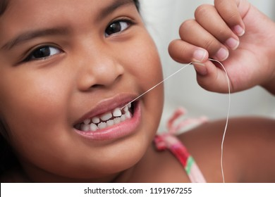Cute girl pulling her loose tooth using a string