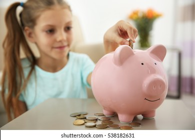 Cute girl putting coins into piggy bank at home