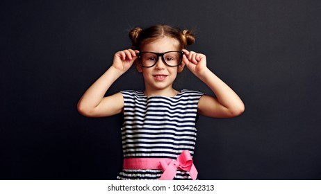 Cute girl putting on optical glasses on black background. Concept of vision correction and treatment.