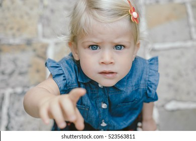 Cute girl reaching finger to camera, pointing.