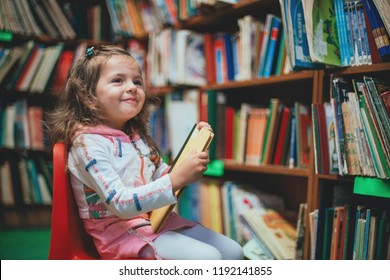Cute girl reading book in library.