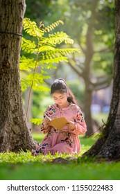 Cute girl reading book on green grass.