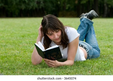 Cute girl reading a book on meadow