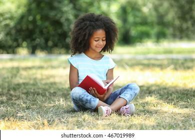 Cute girl reading book on green grass