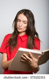cute girl reading a book in a red dress, studio, isolated