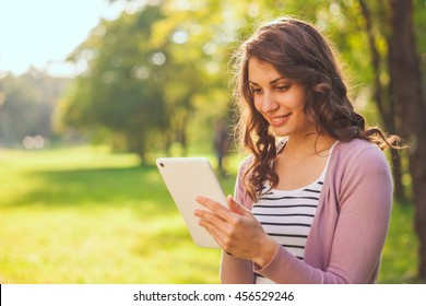 Cute girl reading on her tablet