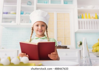 Cute girl reading recipe for cooking