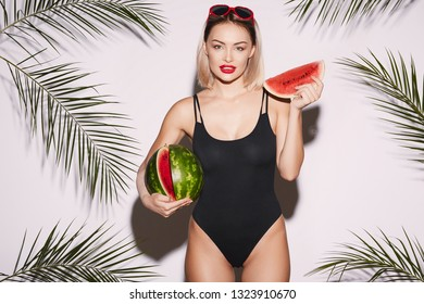 Cute girl with red lips wearing black swimwear and sunglasses posing at white studio background with palms, holding watermelon, looking at camera/
