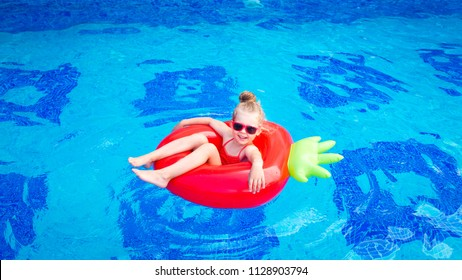 cute girl red swim suit floating in the pool