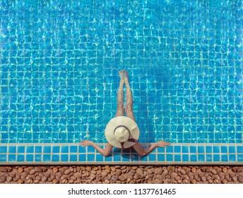 Cute girl is relaxing in the pool.