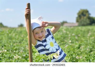 Cute girl resting in potato field