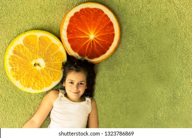 Cute girl resting surrounded by huge slices of orange and lemon (it's pillows). The concept of vitamins, vitamin C, health, juicy and delicious citrus, fruit. ealthy food for children, school
