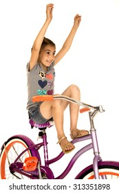 Cute girl riding bicycle hands in air