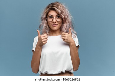 Cute girl in round glasses making thumbs up gesture, approving idea or choice, giving positive opinion, expressing like, showing support and agreement, recommending good product or service