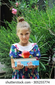 Cute girl , Schoolgirl with books and apple, ready for school. Outdoor photo. Education and kids fashion concept. Fine art image