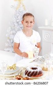 Cute girl setting table for Christmas