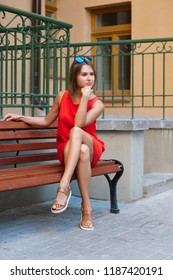 Cute girl in short dress sitting on a bench in the courtyard