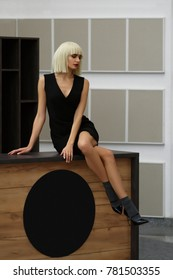 Cute girl in short small black dress and white wig sitting on desk. (image contains noise due to poor lighting conditions)