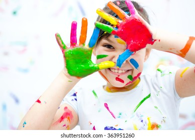 Cute girl showing her hands painted in bright colors