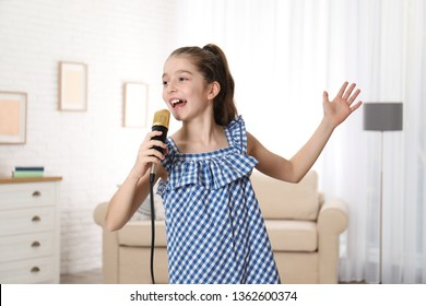 Cute girl singing in microphone at home