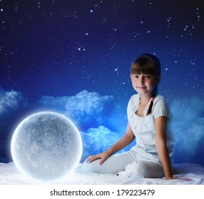 Cute girl sitting in bed with moon