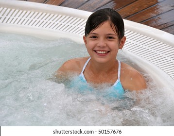 Cute girl sitting in hot jacuzzi.