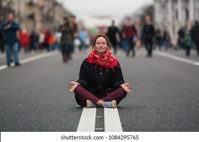 Cute girl sitting in meditation in the middle of a busy street in the city .
