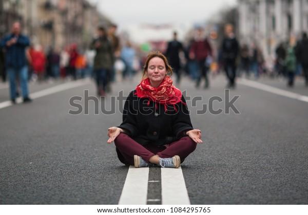 Cute Girl sitzt in Meditation in der Mitte einer belebten Straße in der Stadt .