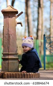 Cute girl sitting near the well