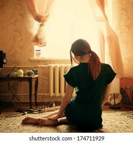 Cute girl sitting on the floor near the window