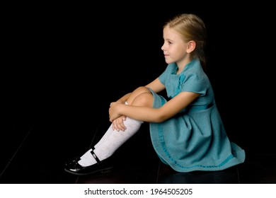 Cute girl sitting on floor hugging her knees