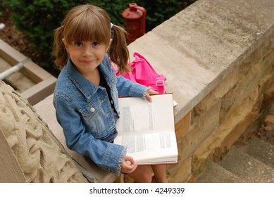 A cute girl sitting on the steps of her school reading a book
