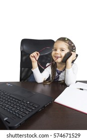 Cute girl sitting at table and doing home tasks