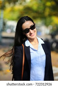 A cute girl smiles in sunglasses and a jacket in the street in the autumn.
