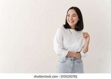 Cute cute girl smiling on a blank wall background. Young woman in hand holds glasses. Place for advertising, copy space.