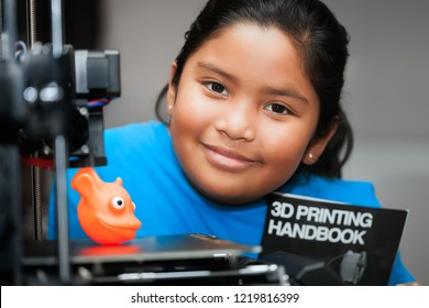 Cute girl smiling and showing her 3d printed creation on the bed of a 3d printer while holding a booklet that teaches about 3d printing.