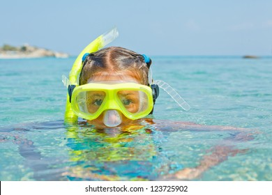 Cute girl snorkelling swimming in the transparent sea