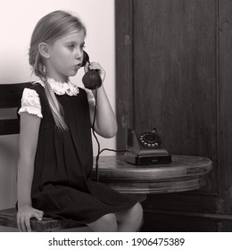 Cute girl speaking via vintage phon