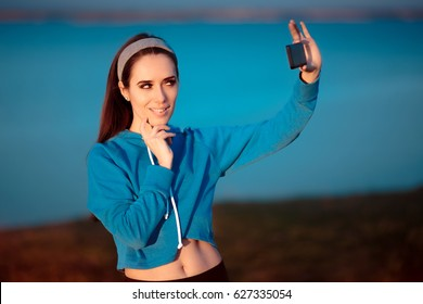 Cute Girl In Sportswear Outfit Taking a Selfie - Funny woman making an expressive face for a self portrait with her Smartphone