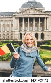 Cute girl stands in the rain with the flag of Belgium against the background of the Royal Palace in Brussels and laughs with the situation. Fall under the rain while traveling. Weather breaks the