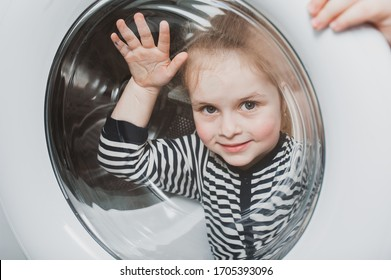 A cute girl in striped clothes peeps out through the round glass door of the washing machine. Cleanliness and Household Concept