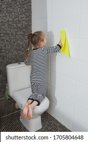 Cute girl in striped clothes washes a yellow rag on the wall. The child cleans at home. Household duties. Cute kid girl cleaning around. The idea of a child's activity during quarantine
