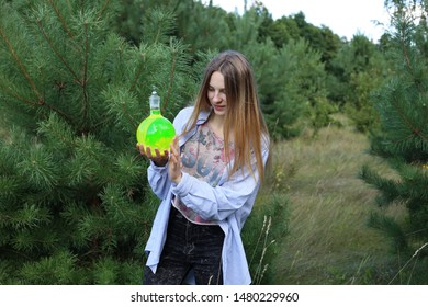 A cute girl student carefully examines a round-bottom flask with green substance, which she carefully holds in her hands.