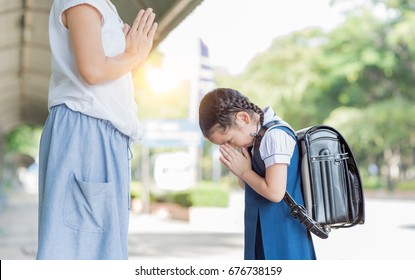 cute girl student pay respect or sawasdee to her mother before going to school.Thai culture
