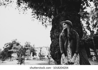 Cute girl in stylish clothes and a hat stands near a big tree and looks thoughtfully aside