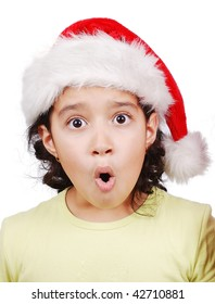 Cute girl with surprised expression on face and santa hat on head