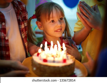Cute girl surrounded by her friends and birthday cake with candles